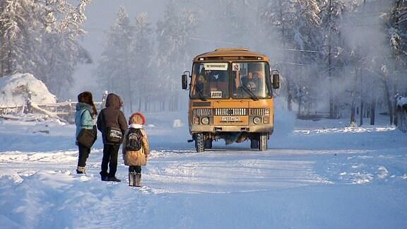 Drei Kinder warten auf den Schulbus, im Schnee.