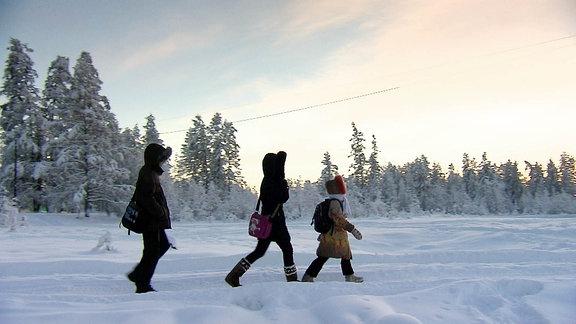 Drei Kinder laufen durch die Winterlandschaft.