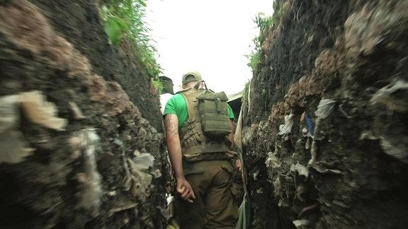 Soldat läuft durch Schützengraben in der Ost-Ukraine