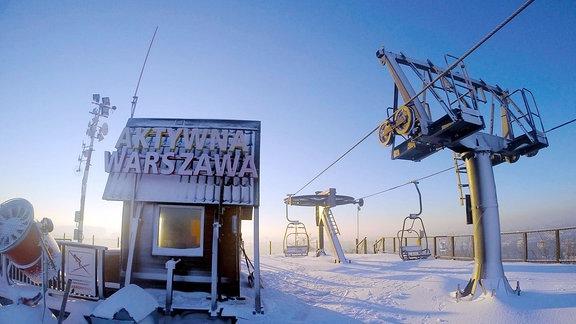 Schild auf Skipiste. Im Hintergrund das Zentrum von Warschau.