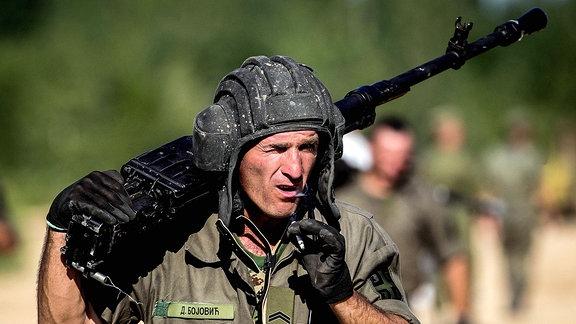 Serbischer Soldat mit Waffe auf Schultern beim Marsch.
