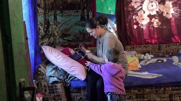Eine Frau füttert ein Kleinkind. Ein anderes kleines Kind greift nach dem Löffel.