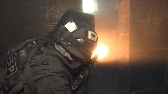 zwei Spezialkräfte in dunklen Uniformen schießen in einen Raum, einer hält einen Schild