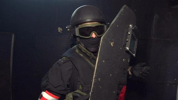 Mitglied der russischen Spezialeinheit Sobr, maskiert, mit Schild, leuchtende Armbinde