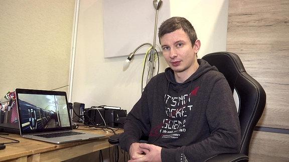 junger Mann im dunklen Sweatshirt sitzt vor Notebook