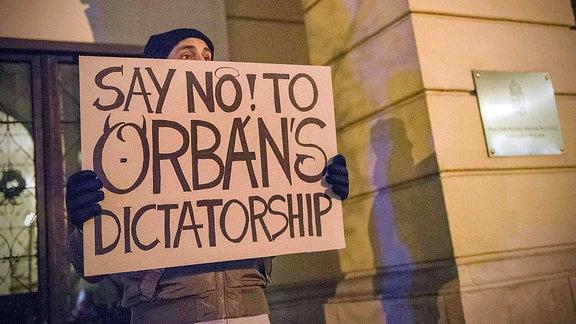 """Eine Person hält ein Schild mit der Aufschrift """"Say no to Orban´s Dictatorship""""."""