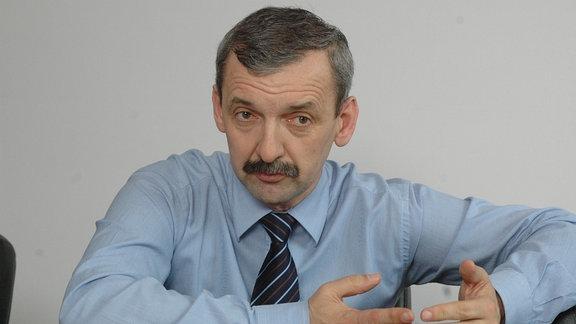 Mann mittleren Alters in Hemd und mit Krawatte sitzt an einem Tisch und erklärt