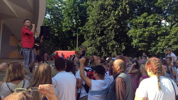 Mann mit Mikrofon, Bühne, Publikum