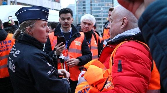 Polizistin mit protestierenden Spediteuren