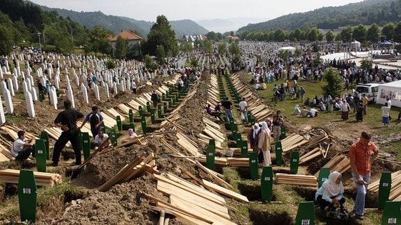 Zehntausende Menschen auf einem Friedhof wollen ihre Angehörigen beerdigen.