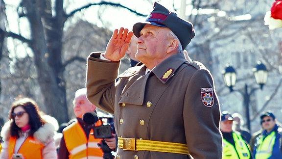Ein litauischer Waffen-SS-Veteran salutiert.