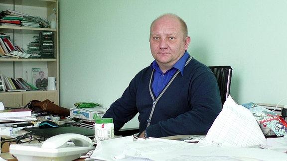 Ein Mann sitzt an einem Schreibtisch.