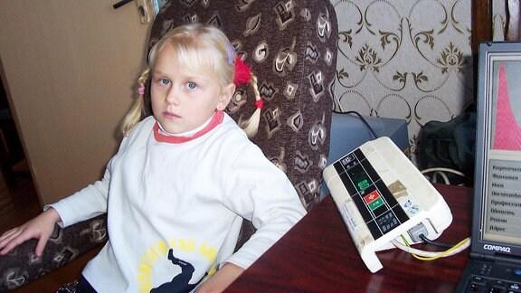 Ein Mädchen sitzt neben einem medizinischen Gerät.
