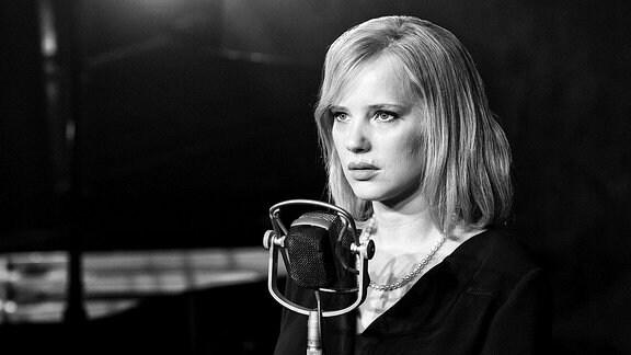 Eine junge Frau steht vor einem Mikrofon.