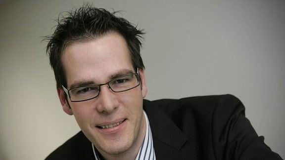 Porträt junger dunkelhaariger Mann mit Brille