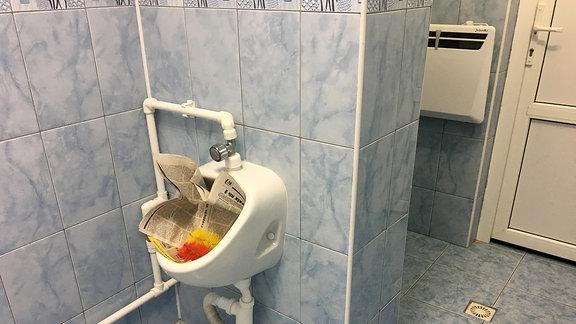 Pissoir mit einer Zeitung verstopft
