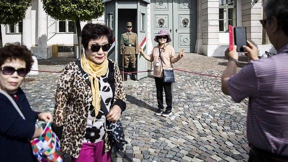 Eine Touristin lässt ein Foto von sich machen vor einem ungarischen Soldaten machen.