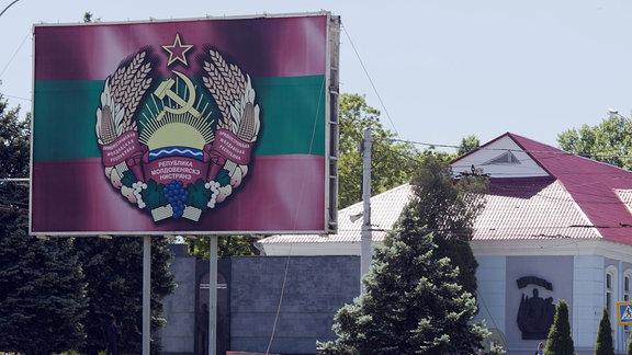 Staatswappen von Transnistrien mit Hammer und Sichel auf einem Aufsteller in Tiraspol.