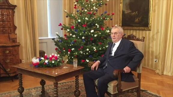 Älterer Mann sitzt neben einem Weihnachtsbaum