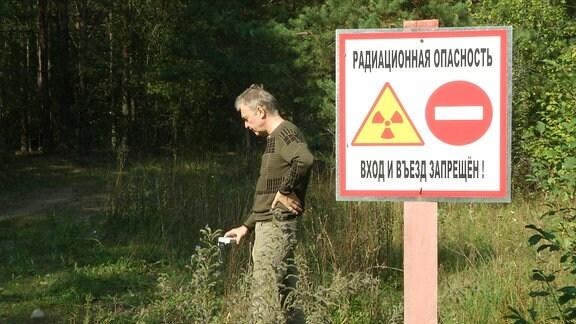 Ein Mann steht neben einem Schild, dass auf die Gefahr von Radioaktivität hinweist und schaut auf seinen Geigerzähler.