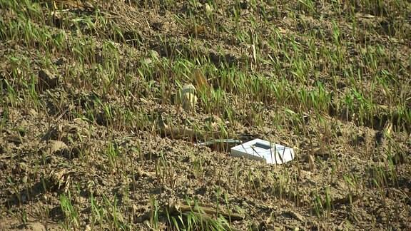 Ein Geigerzähler im Gras auf einem Feld.