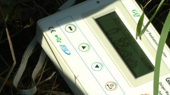 Ein Geigerzähler liegt im Gras.