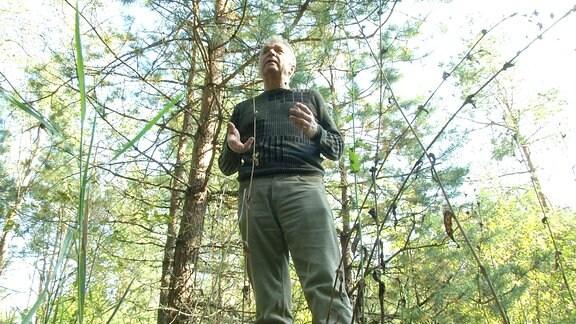 Ein Mann steht im Wald.
