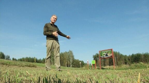 Ein Mann zeigt auf ein Schild auf einem Feld.