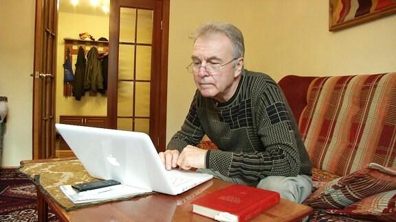 Ein Mann sitzt an seinem Laptop.