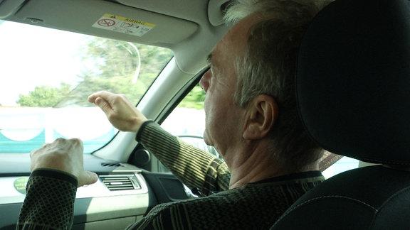 Ein Mann sitzt in einem Auto.