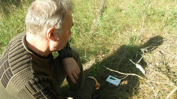 Ein Mann schaut auf einen am Boden liegenden Geigerzähler