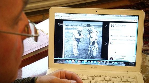 Eine Person schaut Fotos auf einem Laptop an.