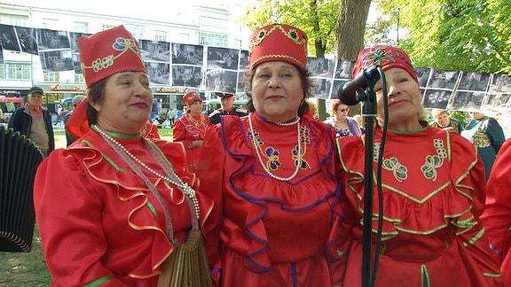 Frauen vor einem Mikrofon in besonderen Gewändern.