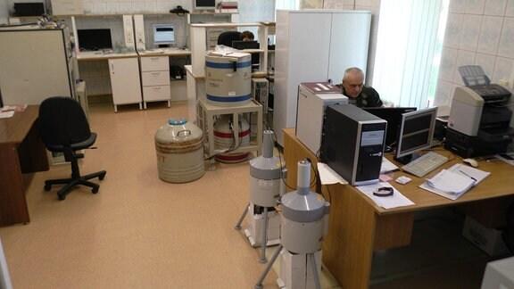 Labor mit diversen Messinstrumenten. Rechts ein Mann am Schreibtisch vor einem Computer.