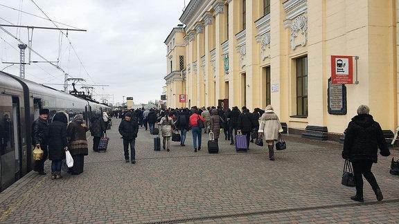 Passanten vor einem Bahnhofsgebäude.