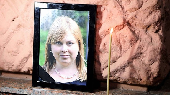 A candle burns by a portrait of perished anti-corruption activist Kateryna Handziuk during a requiem rally outside the Main Department of the National Police in Odesa Region, Odesa, southern Ukraine, November 4, 2018.