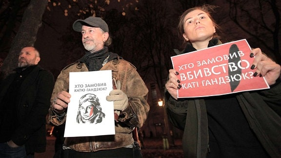 Protesters hold placards during a requiem rally in memory of perished anti-corruption activist Kateryna Handziuk outside the Main Department of the National Police in Kharkiv Region, Kharkiv, northeastern Ukraine, November 4, 2018.