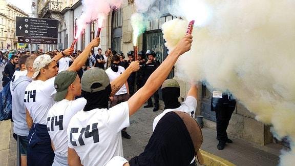 Männer mit S14-T-Shirts halten Bengalfackeln