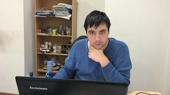 ein Mann vor einem Laptop