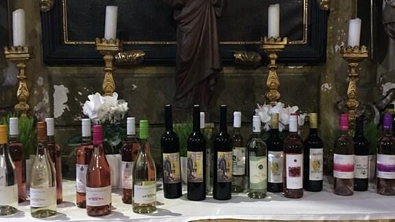 Weinflaschen stehen auf enem Altar