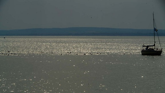 Blick auf den Plattensee in der Dämmerung, Sonnenlicht spiegelt sich in den Wellen
