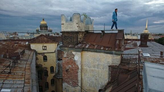 Mann läuft über den Steg eines rostigen Daches in Sankt Petersburg bei stark bewölktem Himmel, Kathedrale mit goldener Kuppel im Hintergrund