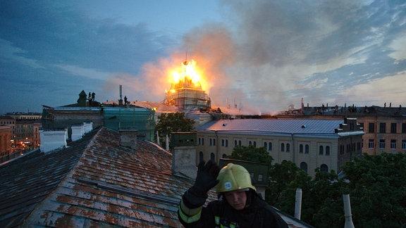 Feuerwehrmann auf einem rostigen Blechdach in Sankt Petersburg, im Hintergrund brennt ein Turm, Löscharbeiten
