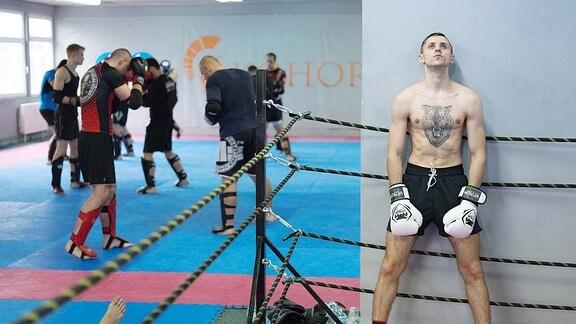 Boxer mit Tattoo auf der Brust lehnt im Rings stehend an Wand. In Hintergrund trainieren andere Boxer.