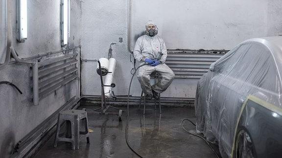 Mann in Ganzkörperschutzanzug mit Lackierpistole sitzt auf einem Hocker neben einem abgeklebten Auto.