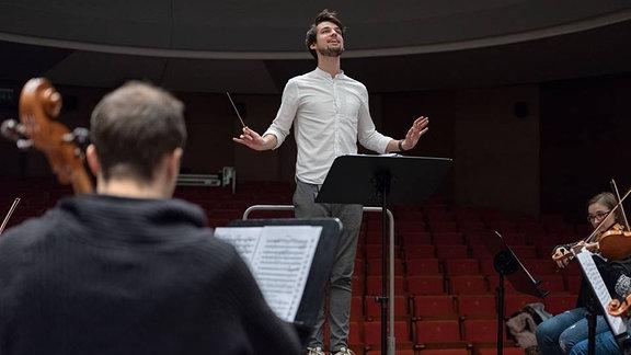 Junger Dirigent mit erhobenem Taktstock vor einem Orchester.