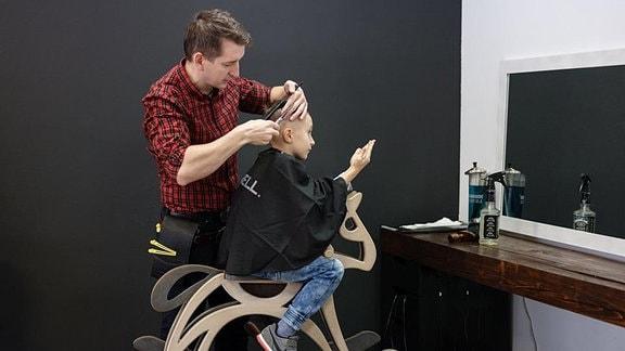 Friseur schneidt Jungem auf einem Schaukelpferd die Haare.