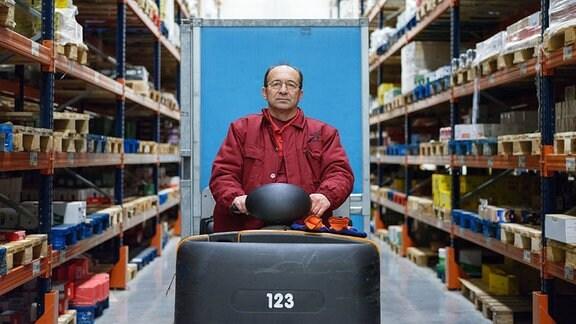 Mann in rotem Overall sitzt auf Gabelstapler in einer Lagerhalle.