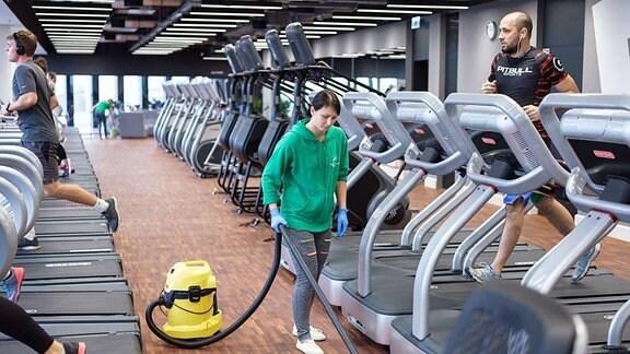 Frau saugt Boden zwischen Laufbändern in einem Fitness-Studio.