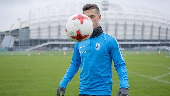 Junger Mann in Sportsachen joungliert vor einem Stadion mit einem Fußball.